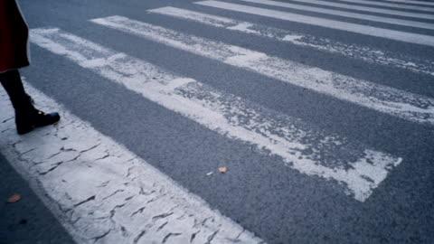 vídeos y material grabado en eventos de stock de joven cruza el paso de peatones - paso peatonal vías públicas