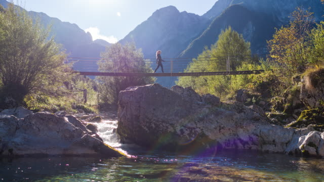 Young woman crossing a suspension bridge over a mountain stream