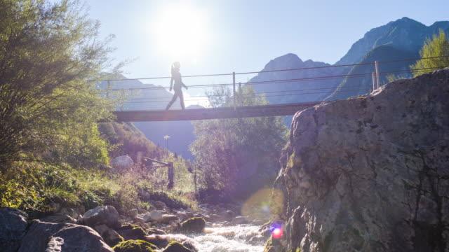 junge frau, die über eine hängebrücke über einen gebirgsbach - überqueren stock-videos und b-roll-filmmaterial
