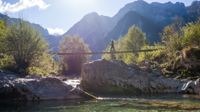 young woman crossing a suspension bridge over mountain stream - wellbeing stock videos & royalty-free footage
