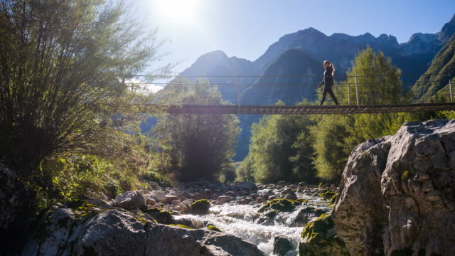 young woman crossing a suspension bridge over mountain stream - idyllic stock videos & royalty-free footage