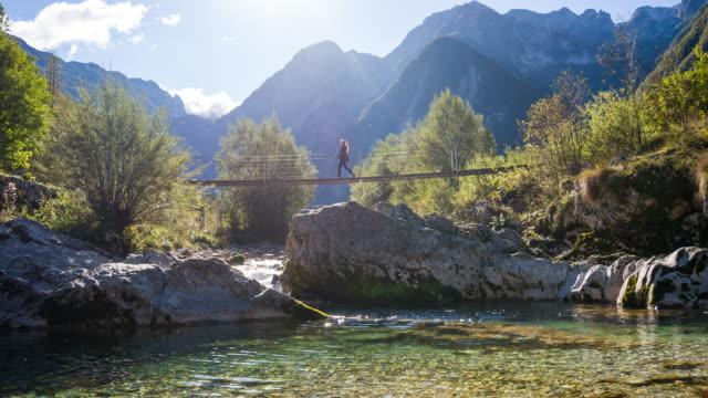 young woman crossing a suspension bridge over mountain stream - suspension bridge stock videos & royalty-free footage