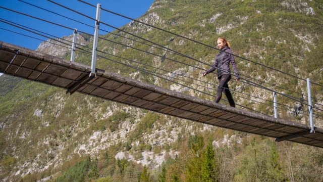 Young woman crossing a wooden suspension bridge in the mountainside