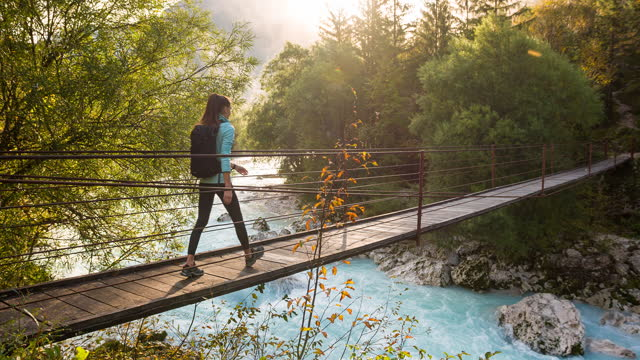 young woman crossing a wooden suspension bridge over mountain stream, vibrant scenery - suspension bridge stock videos & royalty-free footage