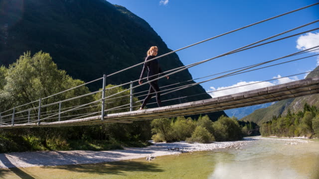 young woman crossing a wooden suspension bridge over mountain stream - suspension bridge stock videos & royalty-free footage