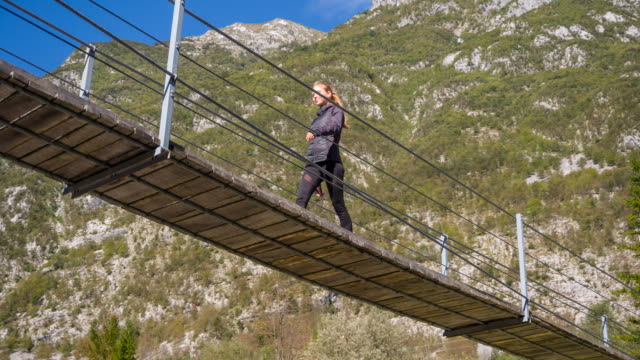 Young woman crossing a wooden suspension bridge over mountain stream