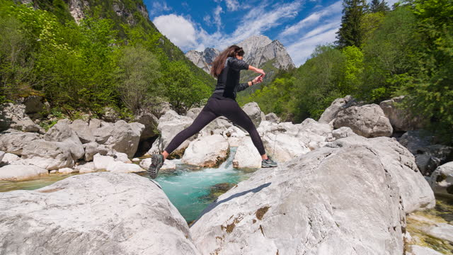young woman crossing mountain river, jumping from rock to rock - outdoor pursuit stock videos & royalty-free footage