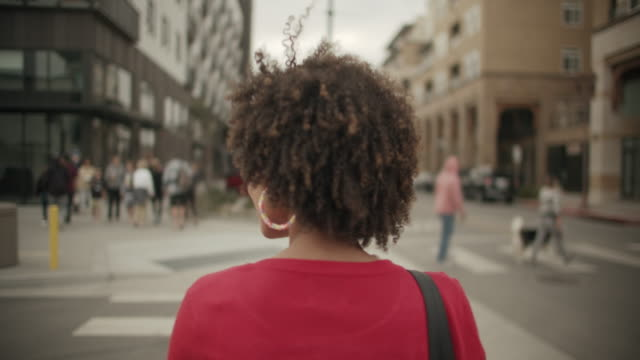 vídeos de stock e filmes b-roll de ms rv young woman crossing the street - afro americano