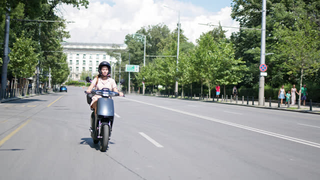 a day in sofia - young woman cruising with rented e-scooter through the city. - crash helmet stock videos & royalty-free footage