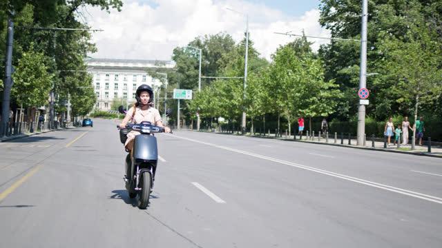 vídeos y material grabado en eventos de stock de a day in sofia - young woman cruising with rented e-scooter through the city. - casco protector