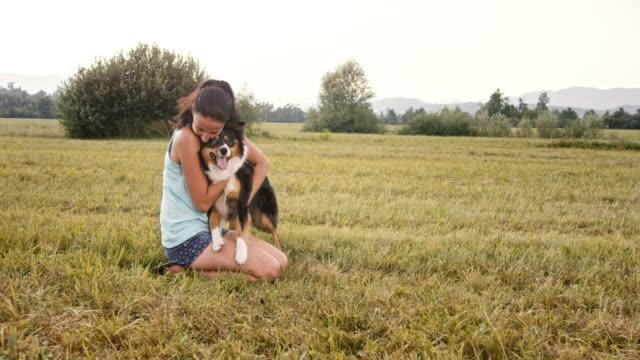 stockvideo's en b-roll-footage met slo mo jonge vrouw haar hond in weide knuffelen - alleen één mid volwassen vrouw