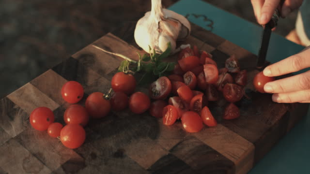 young woman cutting cherry tomatoes on wooden cutting board in sunshine. - italian food stock videos and b-roll footage