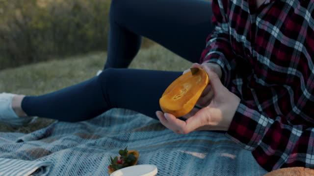young woman cutting fresh mango on picnic blanket - mango stock videos & royalty-free footage