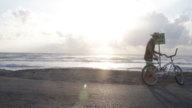 WS Young woman cycles to beach, she leans her bike against a notice then walks onto beach.