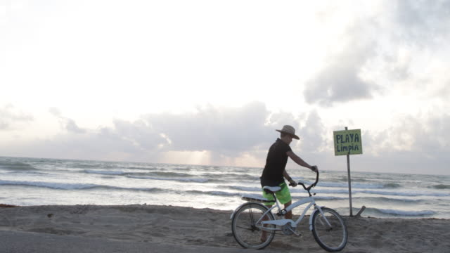 Young woman cycles to beach, she leans her bike against a notice.