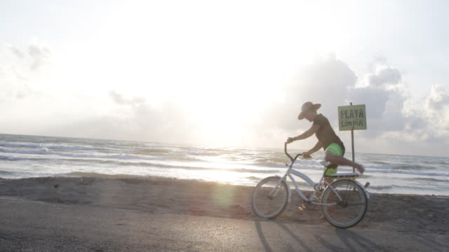 WS Young woman cycles to beach, she leans her bike against a notice.
