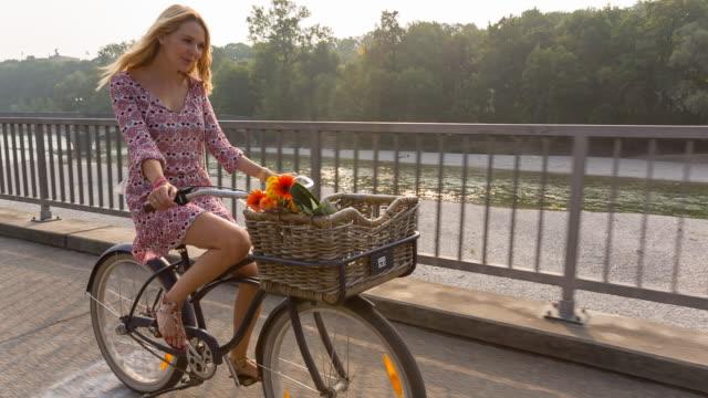Young woman cycling along river