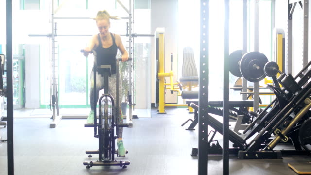 young woman cycling fast on fitness bycicle - step aerobics stock videos and b-roll footage