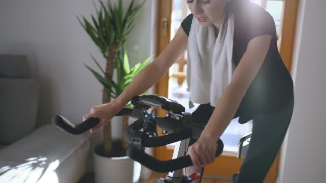 stockvideo's en b-roll-footage met slo mo jonge vrouw die op de oefeningsfiets thuis fietst - 20 24 jaar