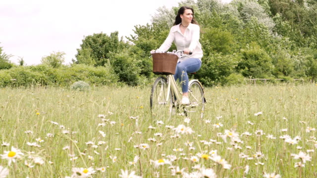 young woman cycling through a meadow, riding a retro bicycle. - tracking shot stock videos & royalty-free footage