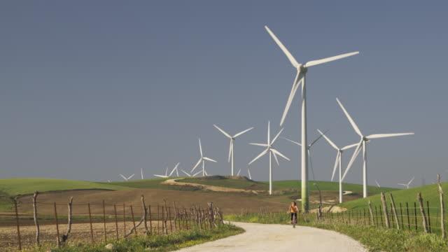 ws young woman cycling through wind farm set in green fields near tarifa / cadiz, spain - approaching stock videos & royalty-free footage