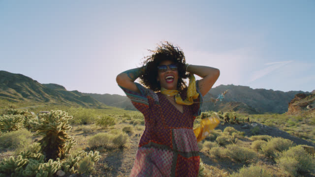 SLO MO. Young woman dances and laughs in the Nevada desert.