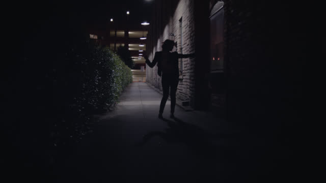 WS SLO MO. Young woman dances and shakes her hair in shadows of city alley at night.