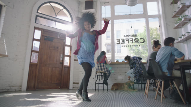 vidéos et rushes de slo mo. young woman dances around sunny downtown coffee shop to music on smartphone with earbuds in and nobody watching. - jeune adulte