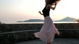 Young woman dances by fence near sea shore in evening