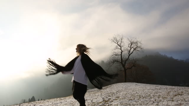 Young woman dances on snow covered grasses in mountain meadow