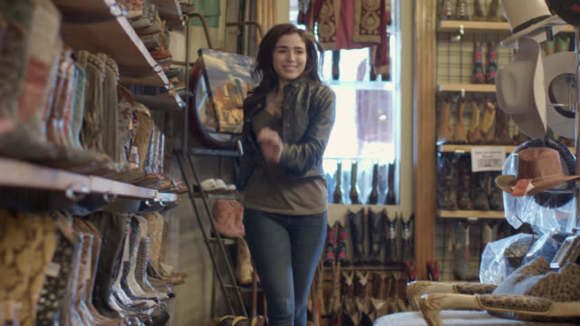 young woman dances up and down aisle in cowboy boots in western store - cowgirl stock videos & royalty-free footage