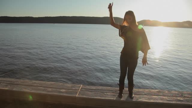 ws young woman dancing and listening mp3 player by river / croton-on-hudson, new york, usa - mindre än 10 sekunder bildbanksvideor och videomaterial från bakom kulisserna