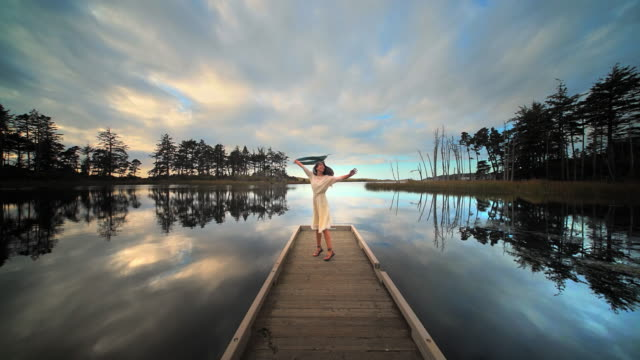 Young woman dancing and twirling on dock of lake at sunset, Oregon