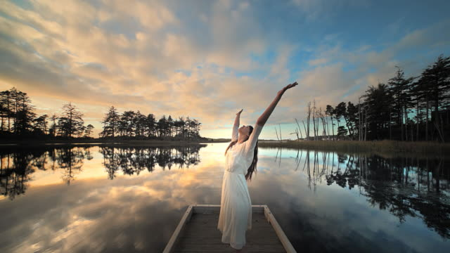 vídeos y material grabado en eventos de stock de young woman dancing and twirling on dock of lake at sunset, oregon - embarcadero