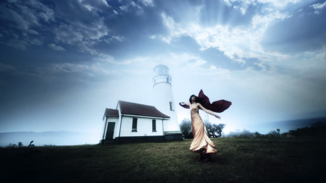Young woman dancing in wind near Cape Blanco Lighthouse, Oregon