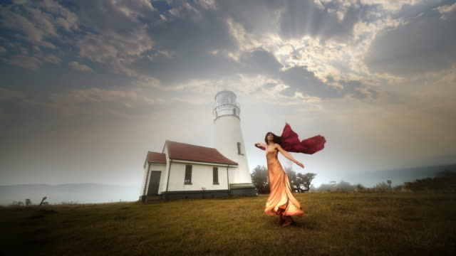 young woman dancing in wind near cape blanco lighthouse, oregon - oregon coast stock videos & royalty-free footage
