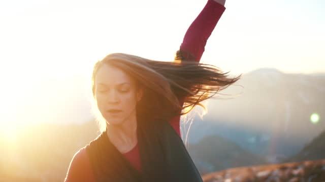 Junge Frau am Gipfel bei Sonnenaufgang tanzen