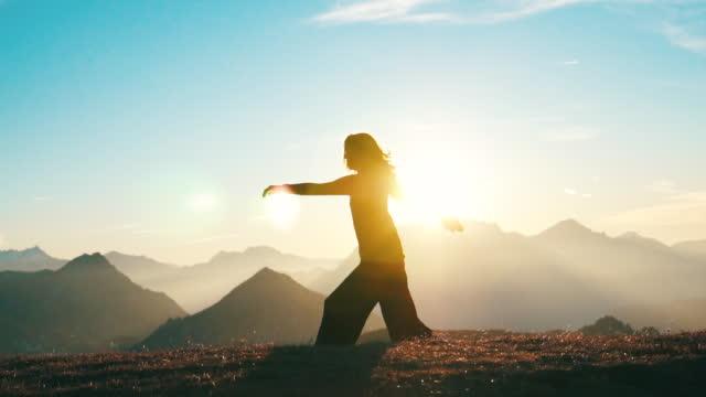 vídeos de stock, filmes e b-roll de jovem mulher dançando no topo da montanha ao nascer do sol - boa postura