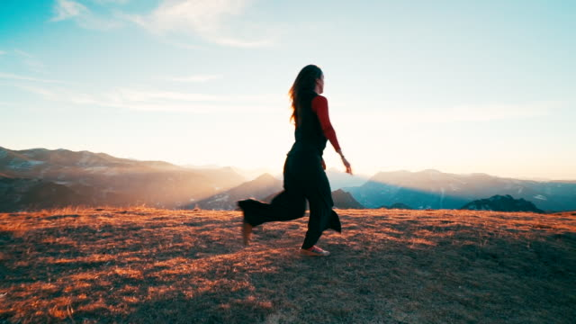 young woman dancing on mountain top at sunrise - im freien stock-videos und b-roll-filmmaterial