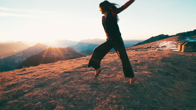 Young woman dancing on mountain top at sunrise