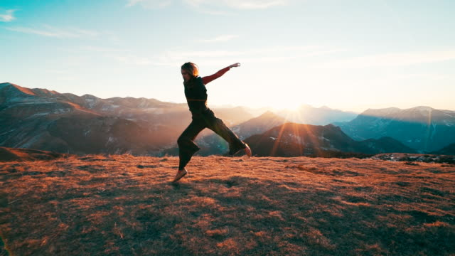 young woman dancing on mountain top at sunrise - tanzkunst stock-videos und b-roll-filmmaterial