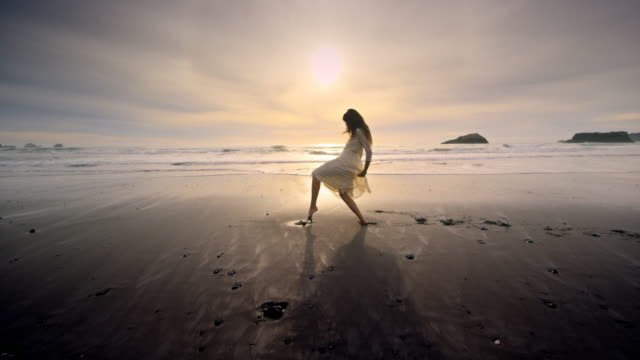 vidéos et rushes de young woman dancing on ocean beach at sunset - danseur
