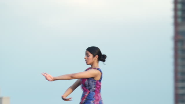 MS PAN Young woman dancing on rooftop, skyscrapers in background, Chicago, Illinois, USA