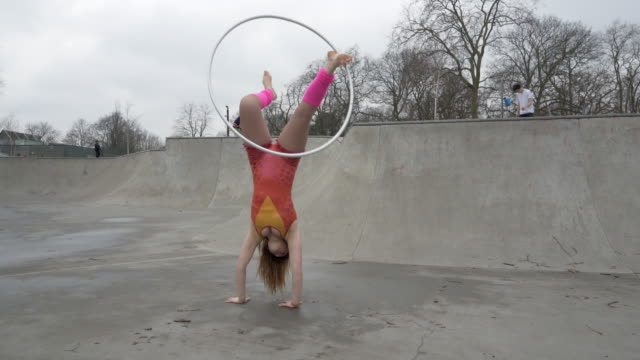 a young woman dancing with hula hoops in a bright costume. - leg warmers stock videos & royalty-free footage