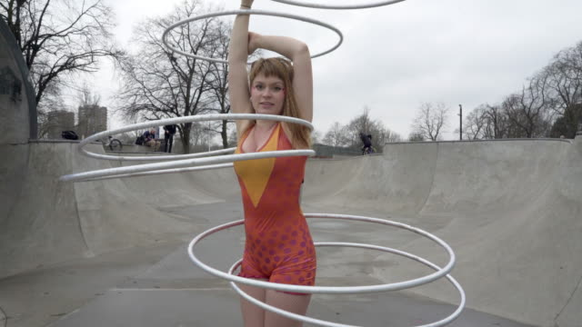 a young woman dancing with hula hoops in a bright costume. - blonde hair stock videos & royalty-free footage