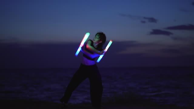 stockvideo's en b-roll-footage met jonge vrouw dansen met verlichting door de zee - kunst