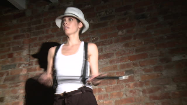 MS Young woman dancing with white hat and cane in front of brick wall, New York City, New York, USA