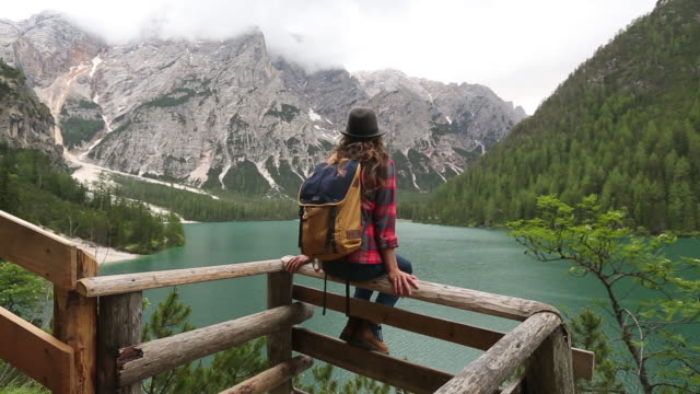 A young woman day hiking in the Dolomite Mountains of Italy.