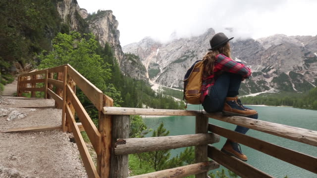 a young woman day hiking in the dolomite mountains of italy. - one mid adult woman only stock videos & royalty-free footage