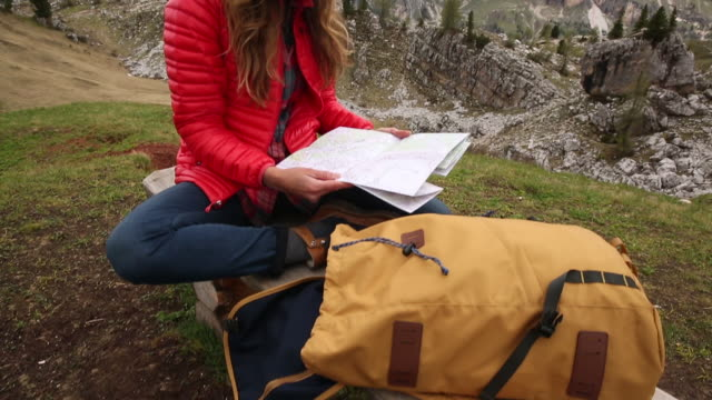 a young woman day hiking in the dolomite mountains of italy. - map stock videos & royalty-free footage